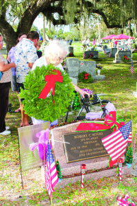 Photo courtesy of Diane Almodovar A relative of Robert C. Myers, who died in Vietnam, places a wreath on his grave for Christmas in December, 2012, at White City Cemetery, Fort Pierce, as part of the Wreaths Across America program honoring fallen troops at Christmastime.