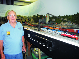 Staff photo by Mary Kemper John Scesny, president of the Treasure Coast Model Railroad and Historical Society, stands next to a section of model railroad depicting a colliery with freight trains at the clubhouse in Port St. Lucie.