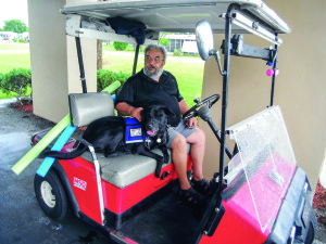 Staff photo by Mary Kemper Tony Santos, an Army Vietnam veteran who lives in Vero Beach, gets ready to take off in his golf cart with his buddy, Shadow, who will one day help be Santos' eyes, ears and hands once service-dog training is completed through Dogs For Life.