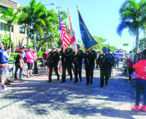 Staff photo by Mary Kemper Members of the Martin County Sheriff's Office carry the Colors down Ocean Boulevard toward Veterans Park in Stuart Nov. 11.