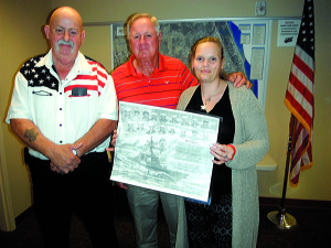 Staff photo by Mary Kemper At the Indian River Veterans Council meeting Jan. 6, Jamie Scott Owens, widow of Ronald Scott Owens, was presented with a special sketch of the USS Cole that included an image of her late husband, who was killed on the ship, along with 16 others, in a terrorist attack on Oct. 12, 2000. To Owens Scott's left is Edward 'Lewie' Lewis, a retired Navy veteran who crafted the sketch, along with Al Scott, her father.