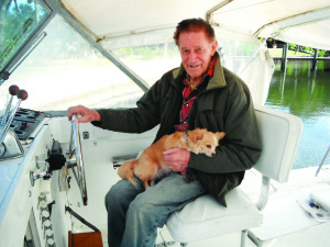 Staff photo by Mary Kemper Dr. Roman A. 'Doc' Swiezy sits at the wheel of his boat in Stuart with 'first mate' 'Fuzzy'  on his lap. At 96, the veterinarian, an Army veteran of World War II, is still practicing.