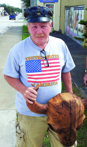 """Photo courtesy of AVET Project Navy veteran Jim McDole holds a small buffalo skull sculpture he made from a bit of Chinese tallow from which he's co-creating """"The First Buffalo Hunt,"""" an 8-foot wood sculpture. McDole is homeless in Cocoa and hopes the sculpture will help him rebuild his life."""