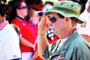 Mitch Kloorfain/chief photographer Bruce Hudson, one of the organizers of the Memorial Day parade in Stuart salutes during the playing of the national anthem.