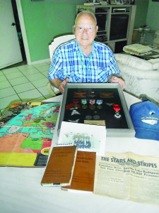 Staff photo by Mary Kemper World War II Navy veteran Rocco 'Rocky' Vasca, Port St. Lucie, is shown at his home surrounded by memorabilia from his service in wartime. Included are, from left, a map of the European theater published in late 1941, showing key battles and engagements up to that point; flight log books; a photo of Vasca's airship crew; a 1941 copy of Stars and Stripes; and a shadowbox case for Vasca's medals and other memorabilia, including, sitting on top, the French Legion d'Honneur, awarded June 5 at a ceremony at Boynton Beach Memorial Veterans Park.