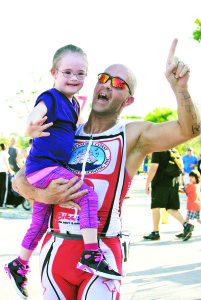 Photo by Maria Isabel  Port St. Lucie Marine Corps and triathlon veteran Chris Bertorelli holds his niece after the first Chasing Caterpillars Triathlon, Feb. 2014. The organizer, Vietnam veteran Jerry Kyckelhahn, of Palm City, has  written a book to help older folks go from couch potato to triathletes. The next Chasing Caterpillars will be on Feb. 21, 2016, in Stuart.