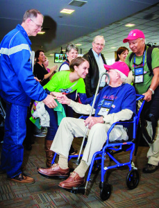 Photo by Phil Galdys World War II Army veteran Vincent Koch is pushed by his guardian, Army veteran Dan Aguilar, Palm City, as he shakes hands with an enthusiastic member of the Honor Flight Ground Crew and greeted by others during his arrival in Washington, D.C., Oct. 24 on the Southeast Florida Honor Flight.