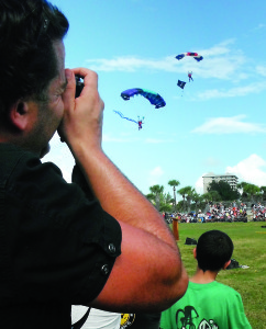 Staff photo by Mary Kemper Excited audience members snap photos of sky divers as they land at the staging ground of the National Navy-UDT SEAL Museum, Fort Pierce, Nov. 7 for the 30th  anniversary of the SEAL Muster.