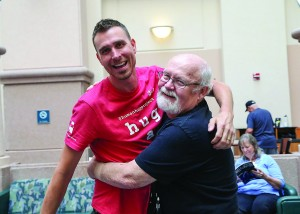 Photo  courtesy of the West Palm Beach VA Medical Center Gino Greganti, cofounder of the Human Hug Project, hugs veteran James Coyle at the West Palm Beach VA Medical Center.